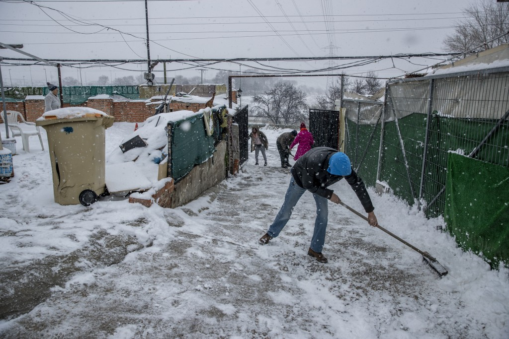 Residents clear the snow at the entrance of a house at the Canada Real shanty town, outside Madrid, Spain, Friday, Jan. 8, 2021. An illegal informal s...