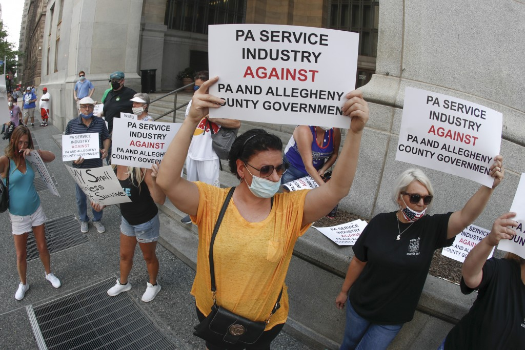 FILE - In this July 2, 2020, file photo, service Industry workers and supporters hold protest signs in front of Allegheny County offices in Pittsburgh...
