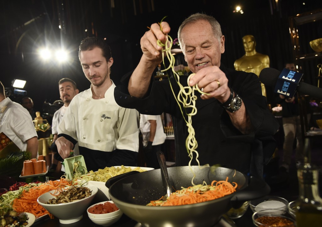FILE - Chef Wolfgang Puck right, and his son Byron make a pasta dish at the Governors Ball Press Preview for the 92nd Academy Awards in Los Angeles on...