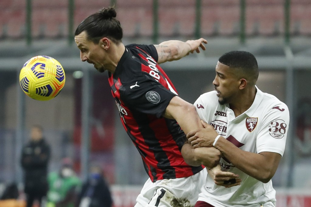 AC Milan's Zlatan Ibrahimovic, left, is challenged by Torino's Gleison Bremer during the Italian Cup round of 16 soccer match between AC Milan and Tor...
