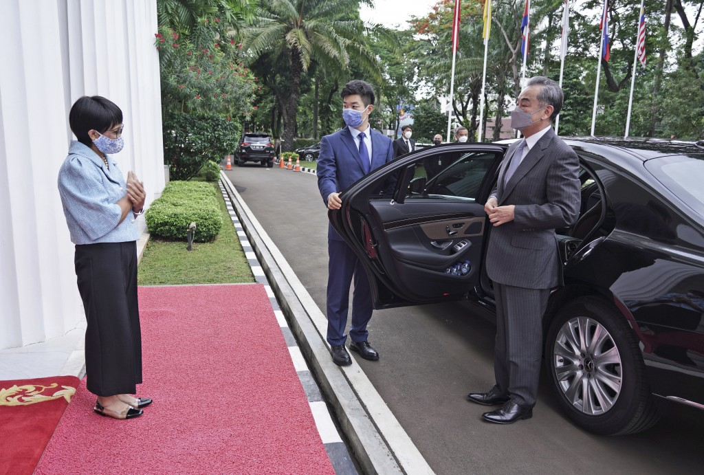 In this photo released by Indonesian Foreign Ministry, Indonesian Foreign Minister Retno Maraud, left, greets her Chinese counterpart Wang Yi upon his...