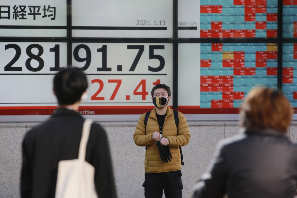 People walk by an electronic stock board of a securities firm in Tokyo, Wednesday, Jan. 13, 2021. Asian stock markets were mixed Wednesday after Wall ...