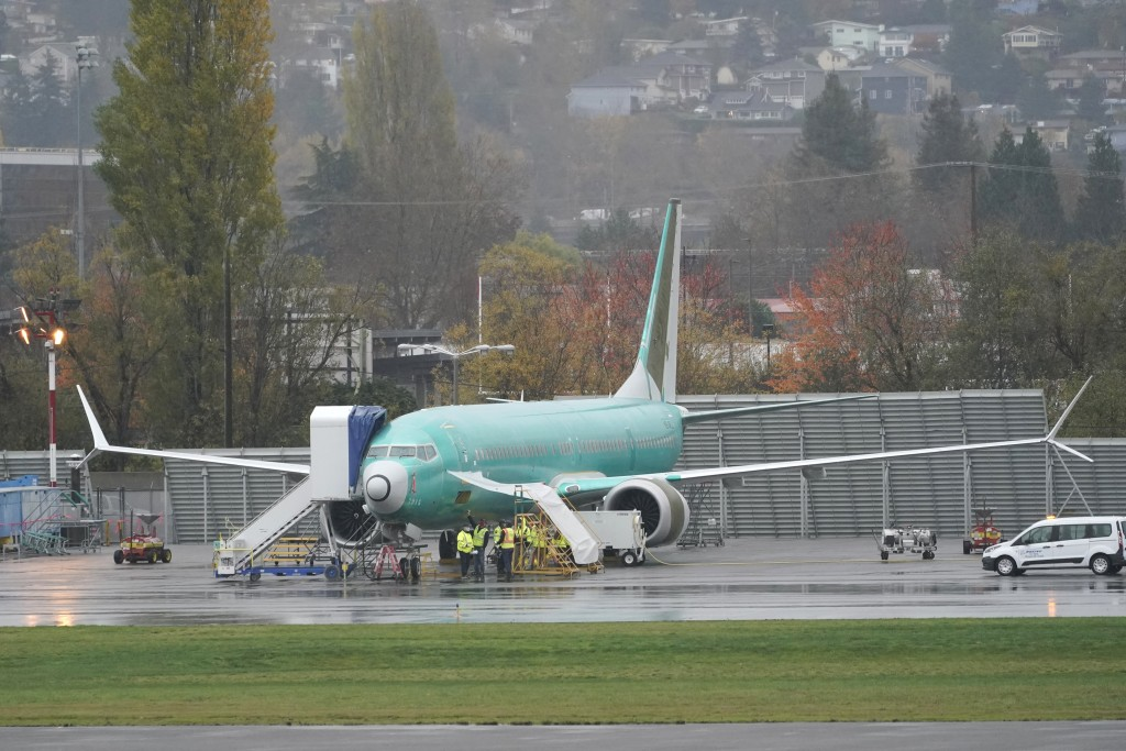 FILE - In this Wednesday, Nov. 18, 2020 file photo, workers stand near a Boeing 737 Max airplane parked at Renton Municipal Airport next to the Boeing...