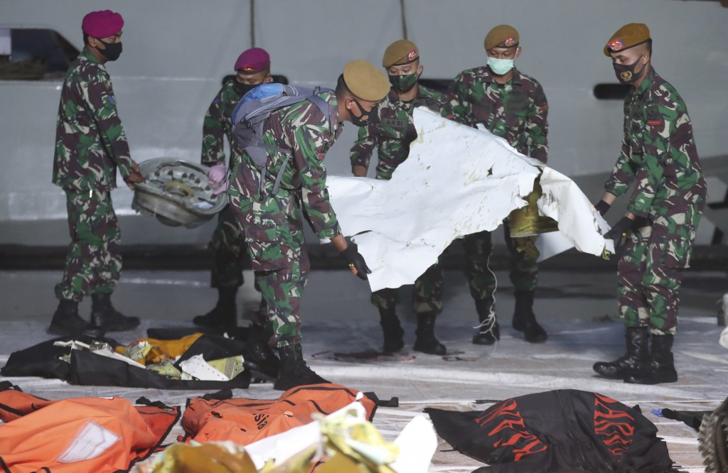 Indonesian soldiers carry pieces of the Sriwijaya Air passenger jet wreckage recovered at the search and rescue command center in Jakarta, Indonesia, ...
