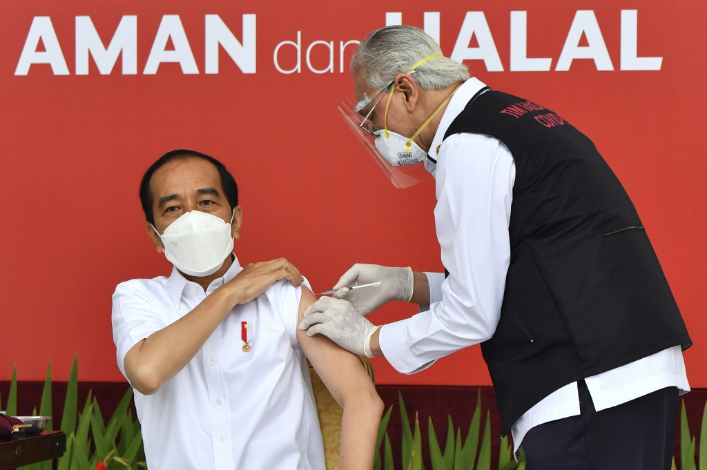 In this photo released by Indonesian Presidential Palace, President Joko Widodo, left, receives a shot of COVID-19 vaccine at Merdeka Palace in Jakart...