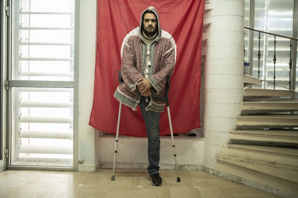 Wael Karrafi, 30, a protester who lost a leg after getting shot during Tunisia's democratic uprising 10 years ago poses for a portrait in Tunis, Tunis...