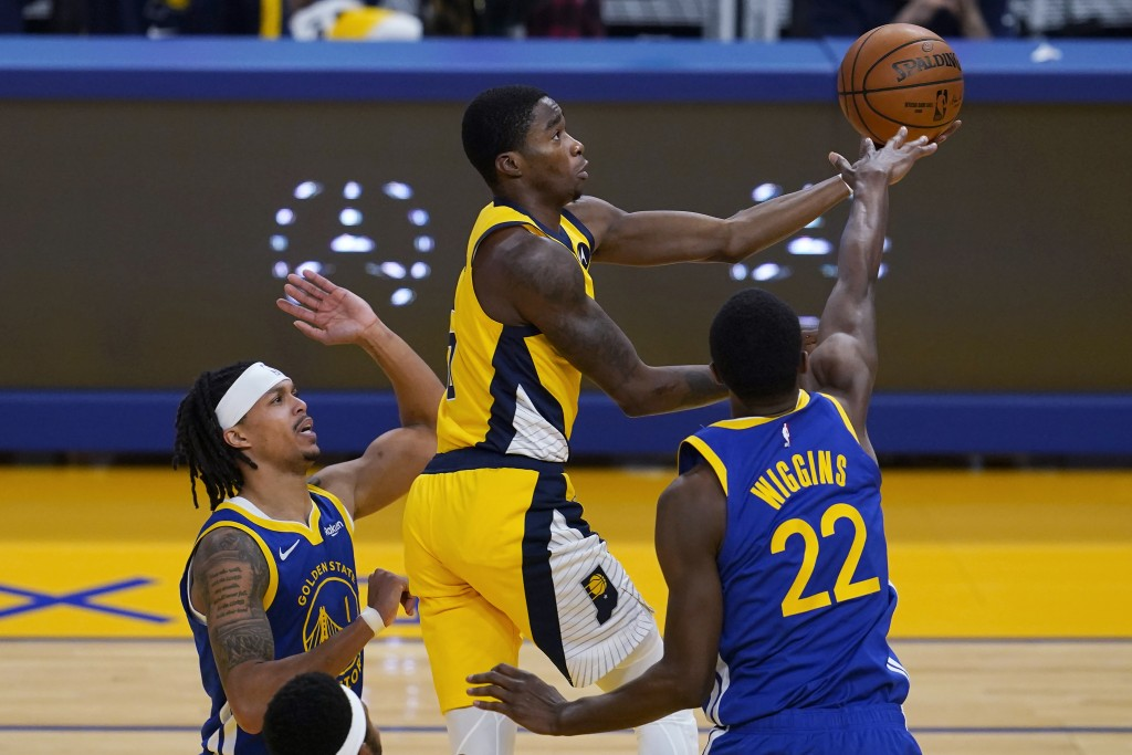 Indiana Pacers guard Edmond Sumner, top, shoots between Golden State Warriors guard Damion Lee, left, and forward Andrew Wiggins (22) during the first...
