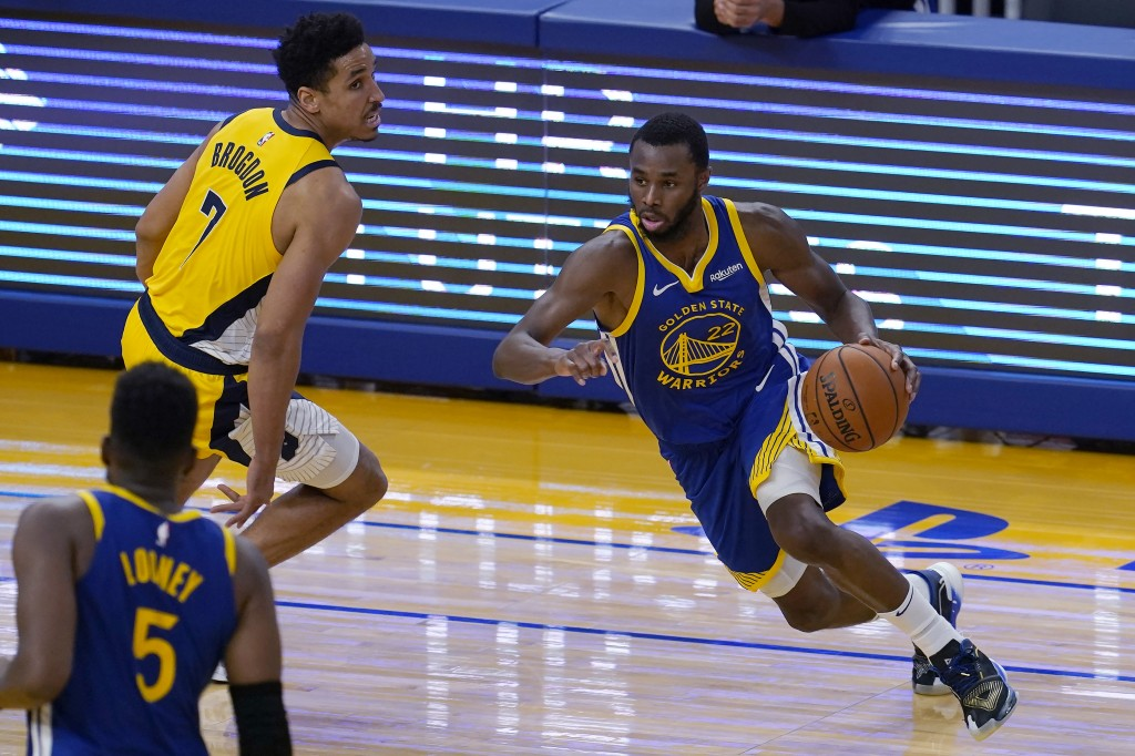 Golden State Warriors forward Andrew Wiggins (22) drives against Indiana Pacers guard Malcolm Brogdon (7) during the first half of an NBA basketball g...
