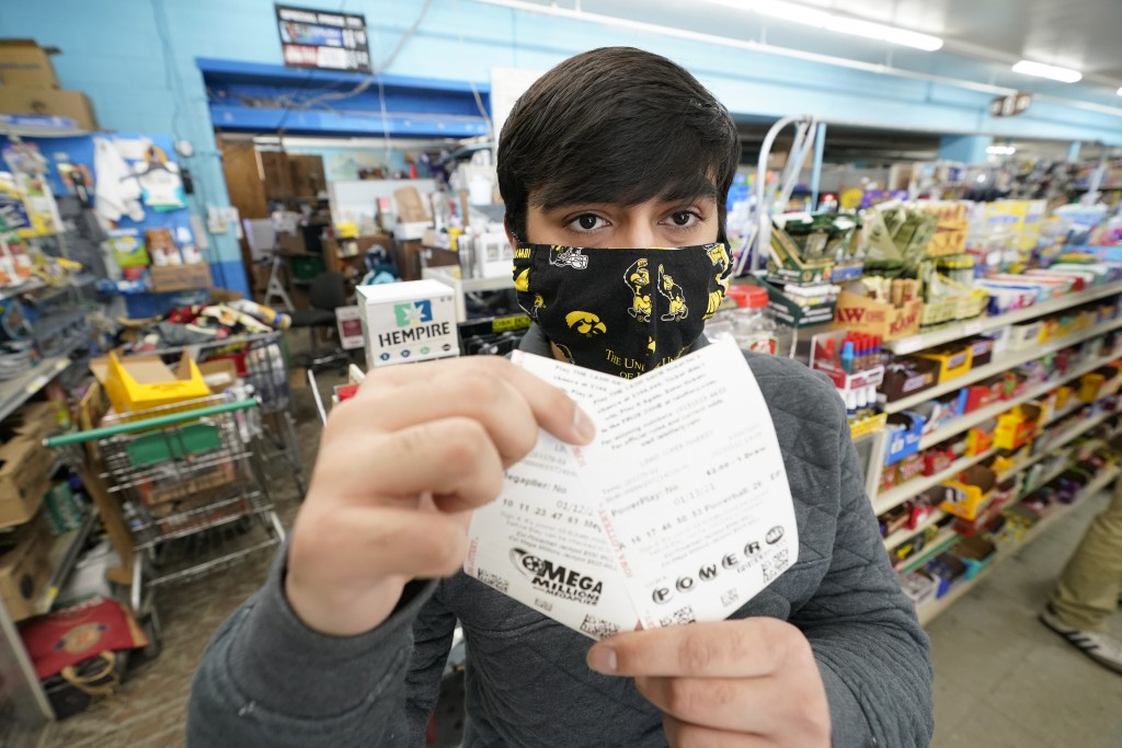 Hardik Kalra, of Des Moines, Iowa, poses for a photo with his Mega Millions and Powerball lottery tickets, Tuesday, Jan. 12, 2021, in Des Moines, Iowa...