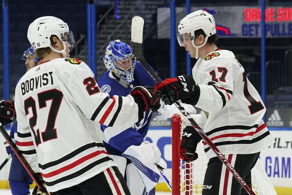Chicago Blackhawks center Dylan Strome (17) celebrates with defenseman Adam Boqvist (27) after Strome scored against the Tampa Bay Lightning during th...