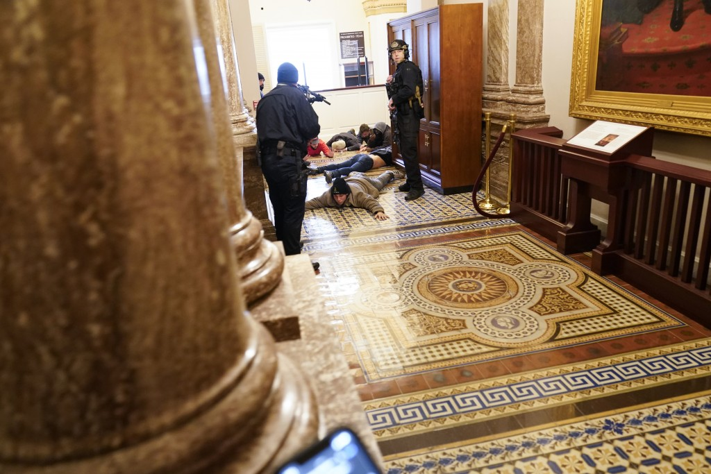 U.S. Capitol Police hold rioters at gun-point near the House Chamber inside the U.S. Capitol on Wednesday, Jan. 6, 2021, in Washington. (AP Photo/Andr...