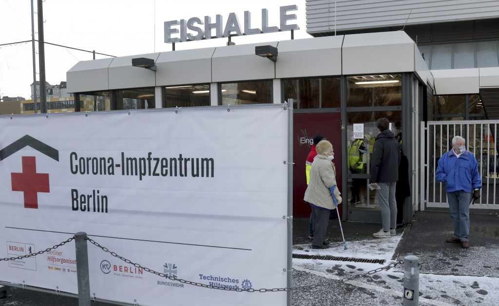 People wait at the entrance of a new open coronavirus, COVID-19, vaccination center in the 'Erika-Hess-Ice-Stadium' in Berlin, Germany, Thursday, Jan....