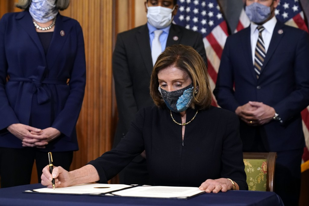 House Speaker Nancy Pelosi of Calif., signs the article of impeachment against President Donald Trump in an engrossment ceremony before transmission t...