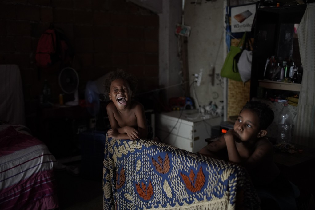 Children play in an occupied building that used to house a factory, amid the new coronavirus pandemic, in Rio de Janeiro, Brazil, Wednesday, Jan. 13, ...