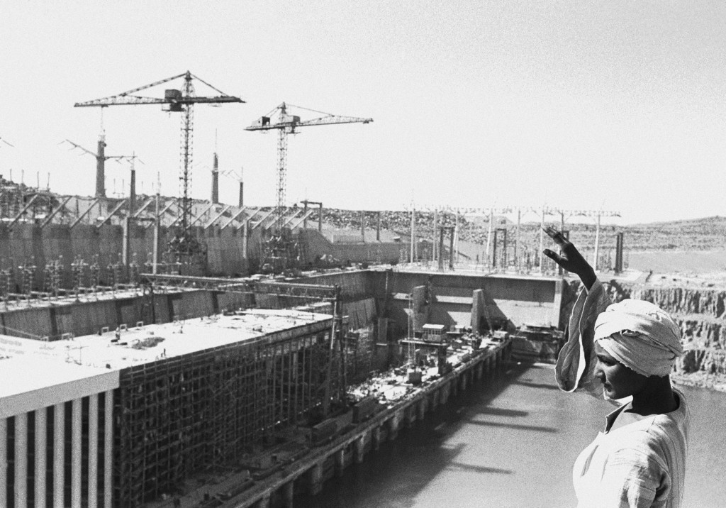 FILE - In this Feb. 27, 1968 file photo, an Egyptian worker waves as he stands on top of a rock overlooking the partly constructed power station on th...