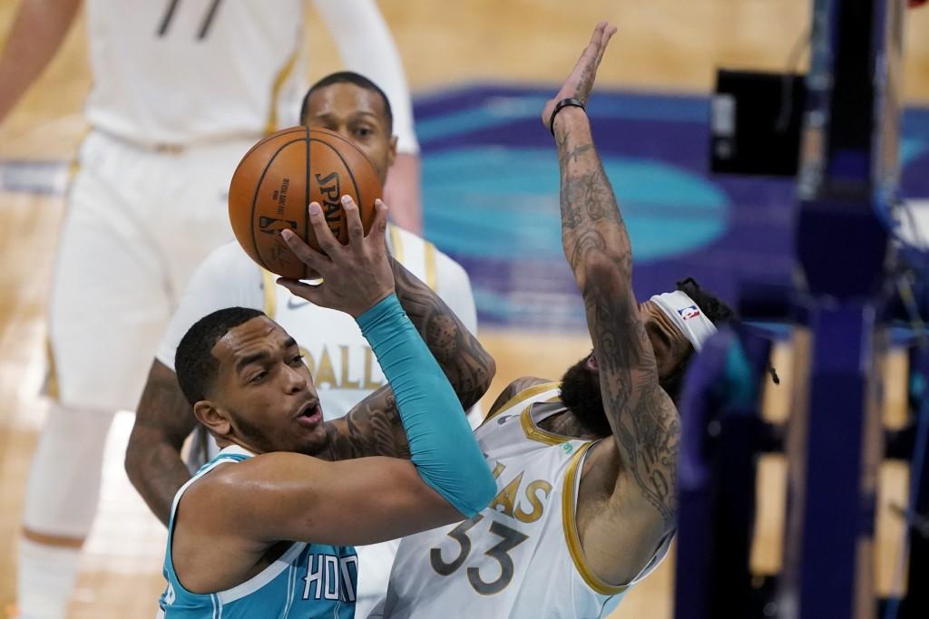 Charlotte Hornets forward P.J. Washington shoots over Dallas Mavericks center Willie Cauley-Stein during the first half of an NBA basketball game in C...
