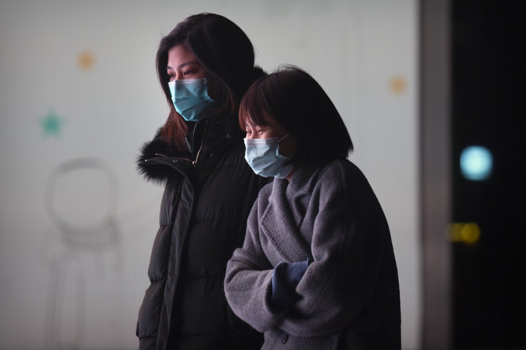 People wearing face masks to protect against the spread of the coronavirus walk outside of an office complex in Beijing, Wednesday, Jan. 13, 2021. Chi...