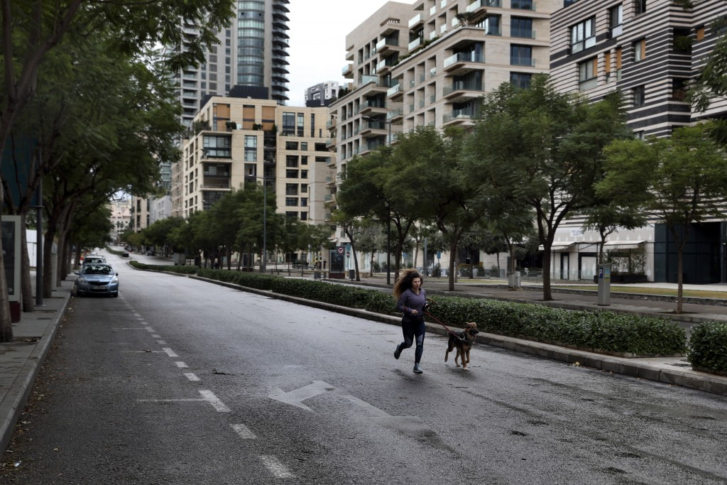 A woman runs with her dog in an almost empty street during a lockdown aimed at curbing the spread of the coronavirus, in Beirut, Lebanon, Thursday, Ja...