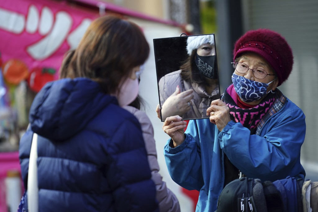 A shopper wearing a protective mask to help curb the spread of the coronavirus uses a mirror as she tries on a hat in a shopping street in Tokyo Thurs...