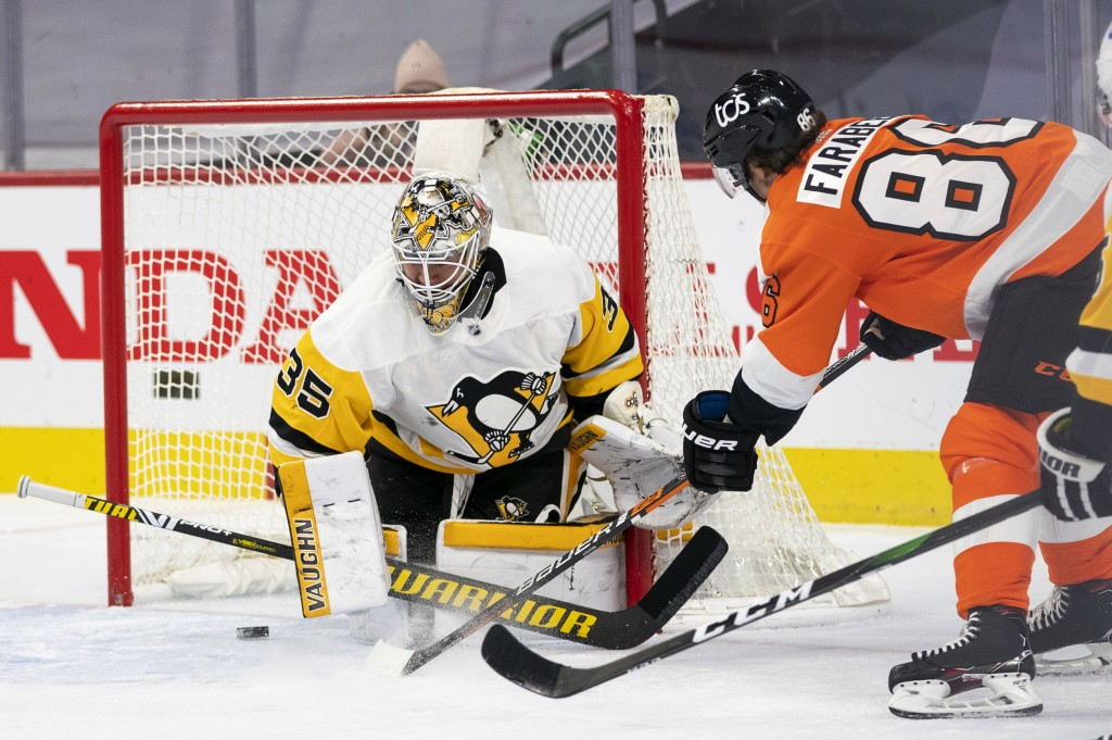 Philadelphia Flyers' Joel Farabee, right, scores a goal on Pittsburgh Penguins goaltender Tristan Jarry during the second period of an NHL hockey game...