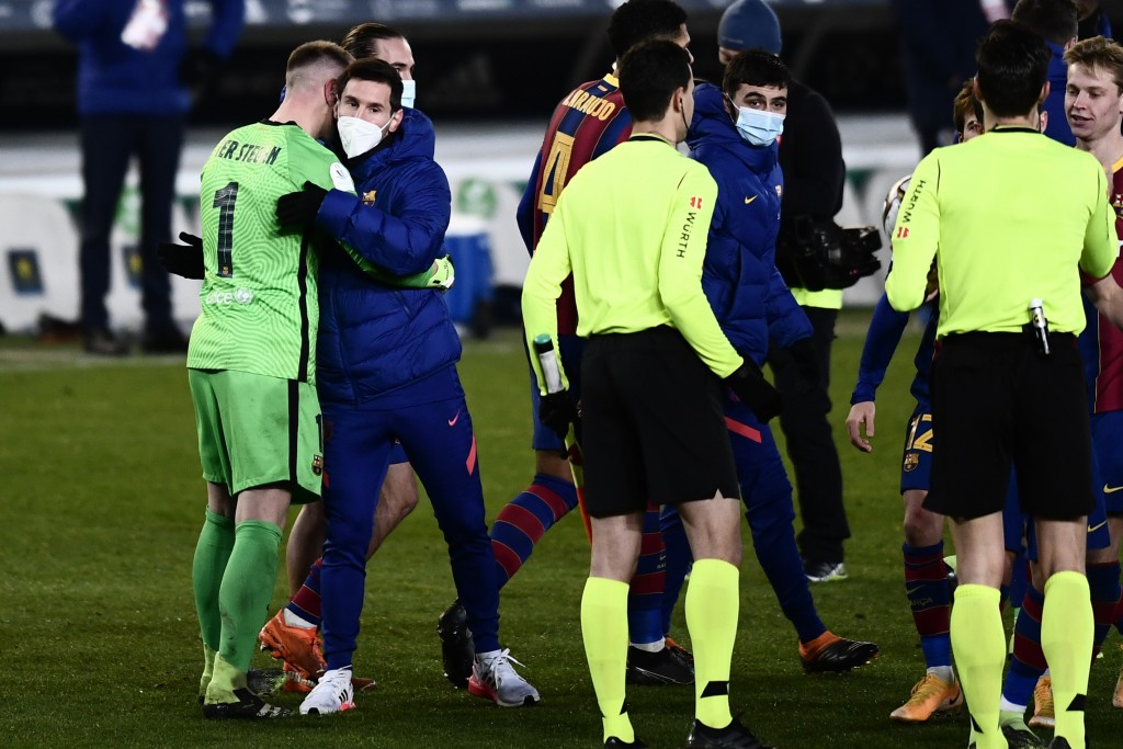 Barcelona's goalkeeper Marc-Andre ter Stegen, left, is greeted by teammate Lionel Messi at the end of the Spanish Super Cup semi final soccer match be...