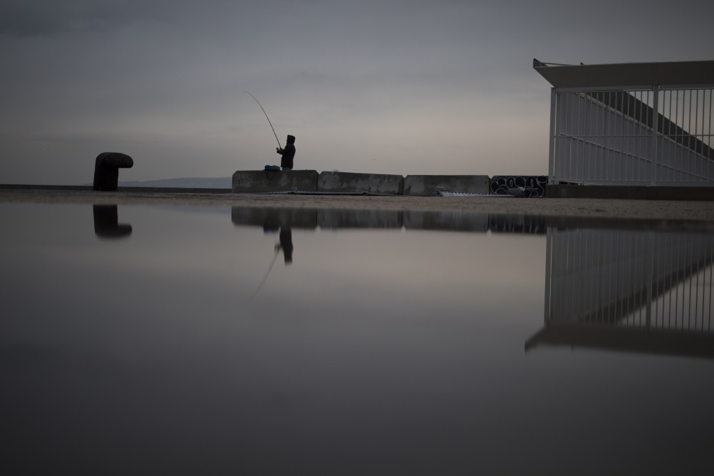 FILE - In this Jan. 10, 2021 file photo, a fisherman reels in his line before a curfew is enforced in Marseille, southern France. Trying to fend off t...