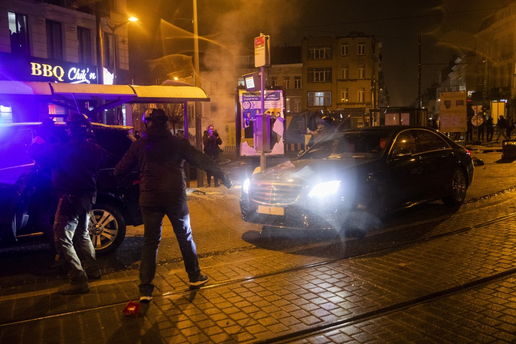 The escorted official car of Belgium's King Philippe makes a turn to avoid protestors in the Belgium capital, Brussels, Wednesday, Jan. 13, 2021, at t...