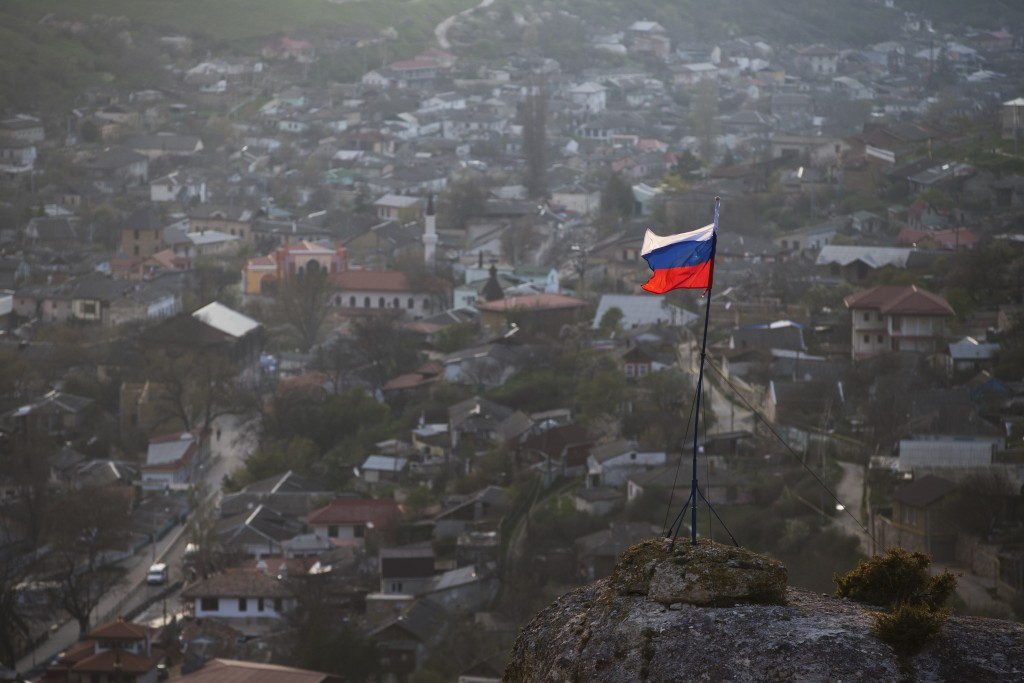 FILE - In this March 28, 2014 file photo, a Russian national flag flies on a hilltop near the city of Bakhchysarai, Crimea. The European Court of Huma...
