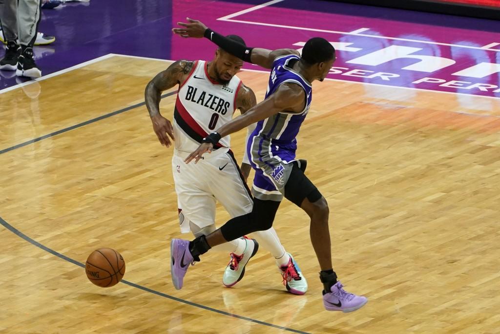 Portland Trail Blazers guard Damian Lillard, left, dodges Sacramento Kings guard De'Aaron Fox, right, during the second quarter of an NBA basketball g...