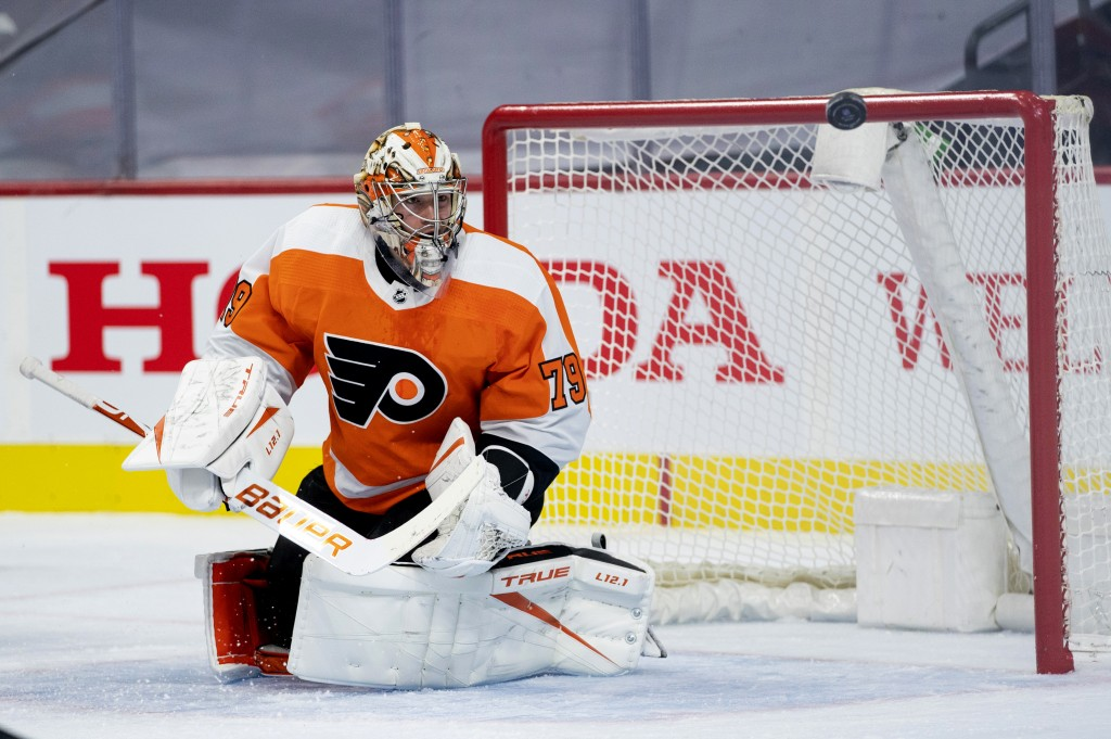 Philadelphia Flyers' goaltender Carter Hart watches as the puck flies away from him during the first period of an NHL hockey game against the Pittsbur...