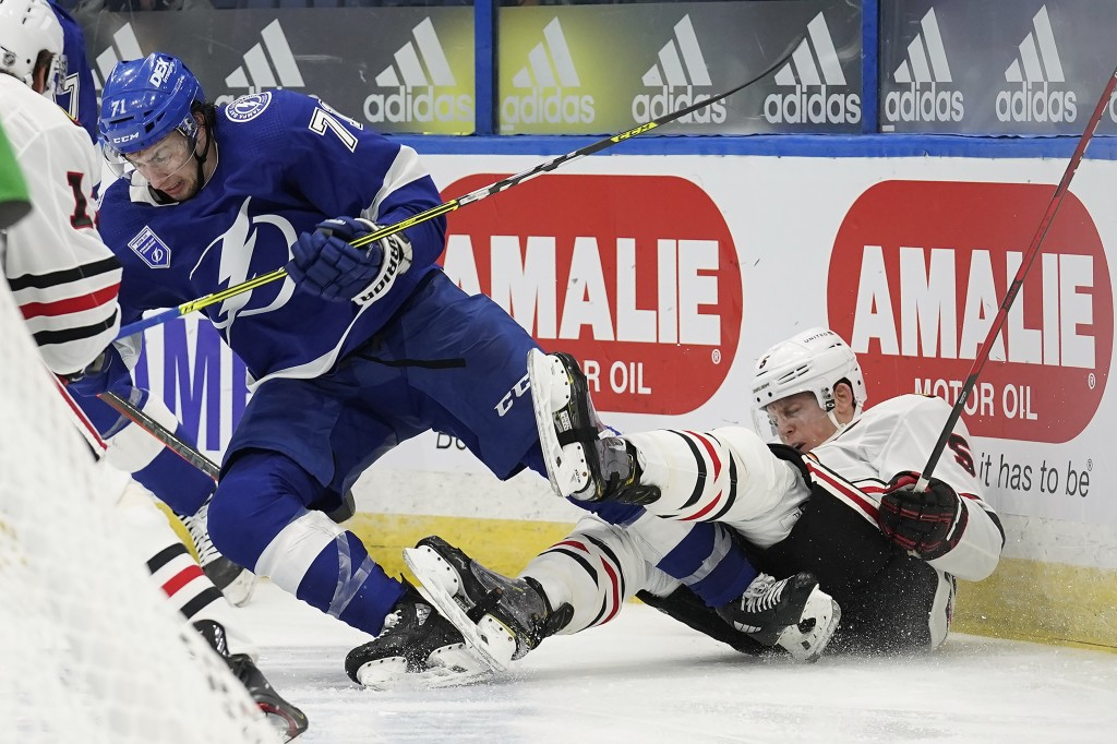 Tampa Bay Lightning center Anthony Cirelli (71) sends Chicago Blackhawks defenseman Connor Murphy (5) into the dasher with a check during the second p...