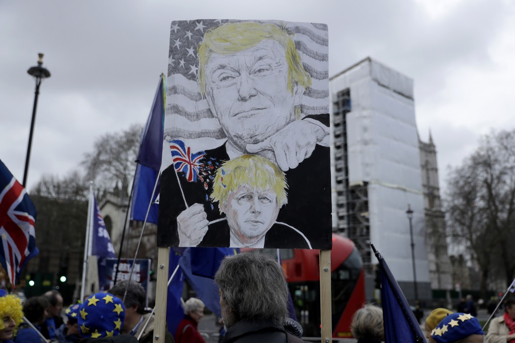 FILE - In this Jan. 8, 2020 file photo remain in the European Union, anti-Brexit protesters, including one with a placard depicting British Prime Mini...