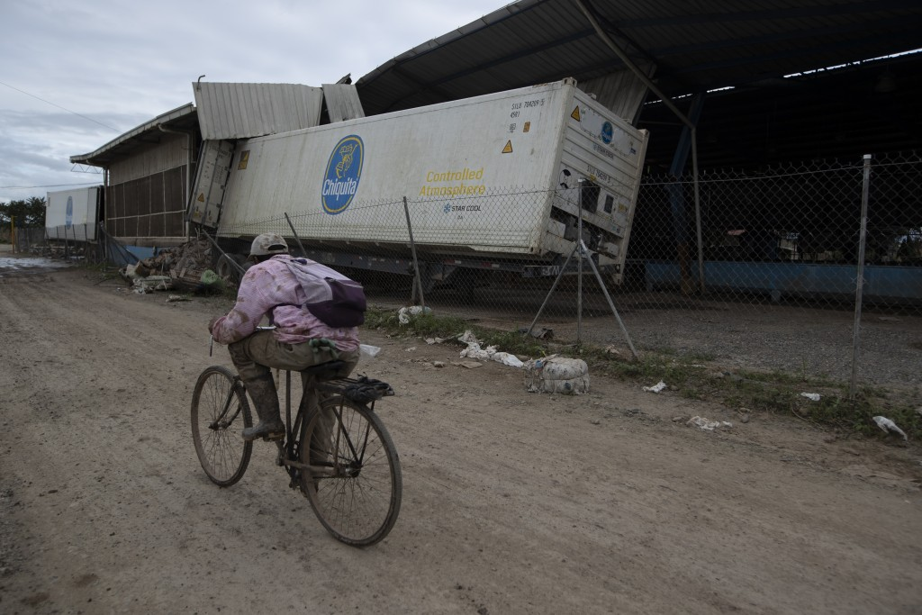 A worker rides his bike past a ravaged banana packing plant severely damaged by hurricanes Eta and Iota in La Lima, Honduras, Wednesday, Jan. 13, 2021...