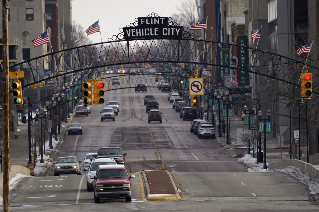 Vehicles drive through downtown Flint, Mich., Wednesday, Jan. 13, 2021. Some Flint residents impacted by months of lead-tainted water are looking past...