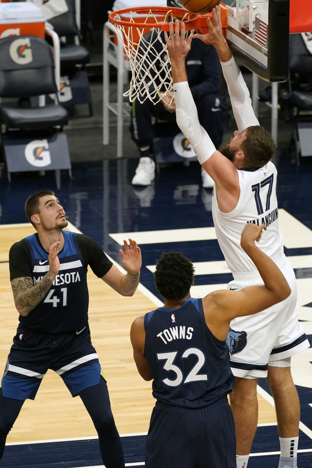 Memphis Grizzlies' Jonas Valanciunas (17) lays up a shot as Minnesota Timberwolves' Juancho Hernangomez (41) and Karl-Anthony Towns watch in the first...