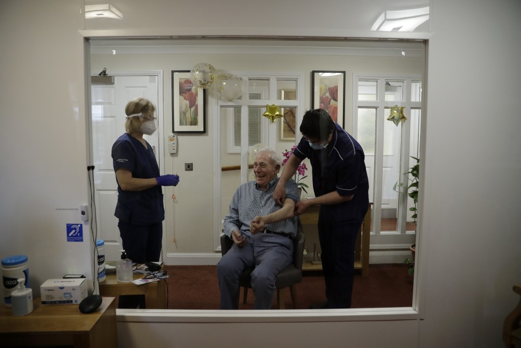 Care home resident Ian Hurley, aged 80, is seen smiling through a viewing screen installed for residents to safely receive visits from family members ...