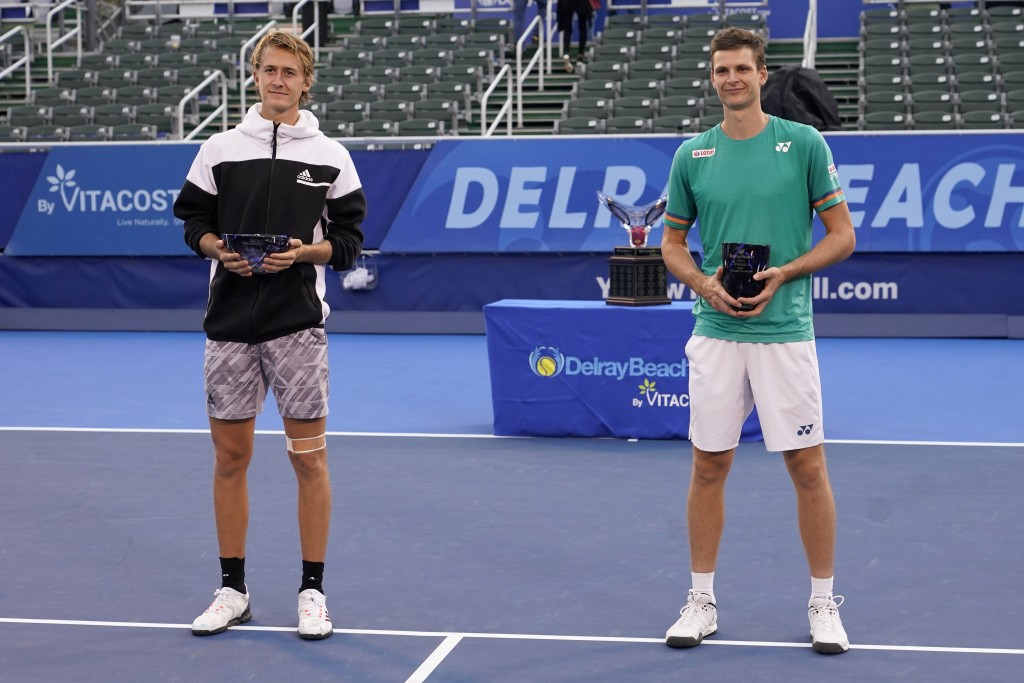 Sebastian Korda, left, and Hubert Hurkacz of Poland, right, pose with their trophy after the men's singles final of the Delray Beach Open tennis tourn...