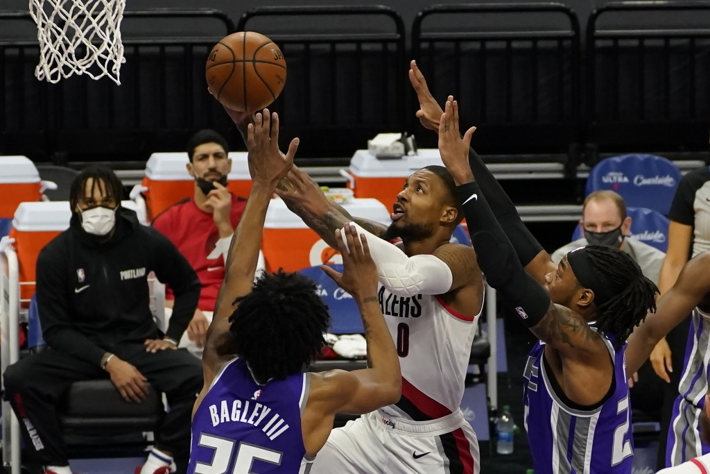 Portland Trail Blazers guard Damian Lillard, right, goes to the basket between Sacramento Kings' Marvin Bagley III, left, and Richaun Holmes, right, d...