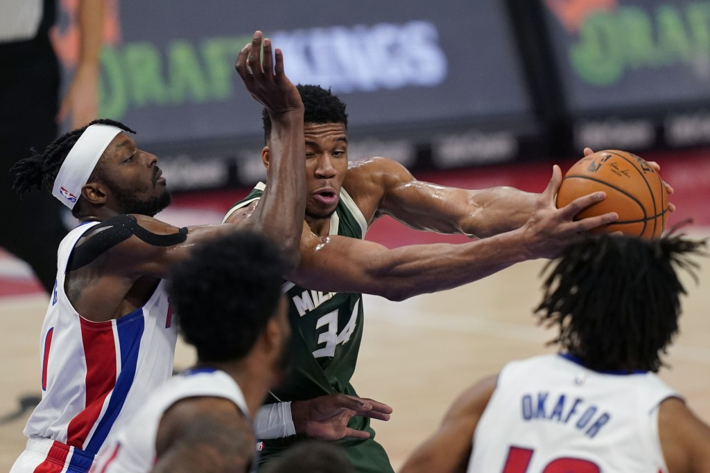 Milwaukee Bucks forward Giannis Antetokounmpo (34) is fouled by Detroit Pistons forward Jerami Grant during the first half of an NBA basketball game, ...