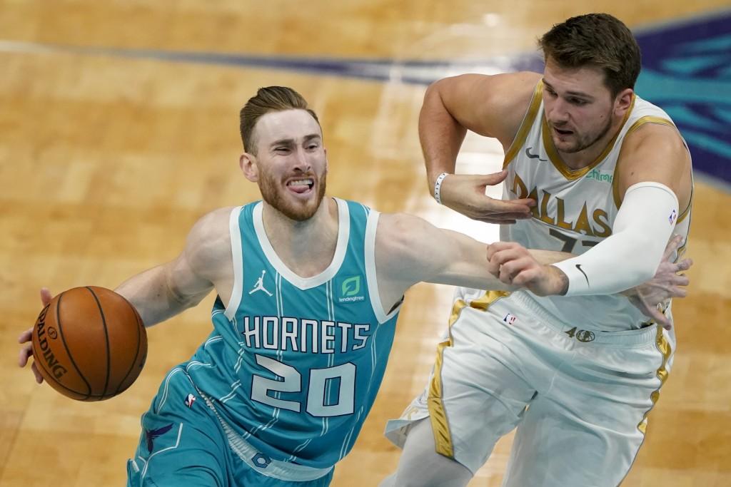 Charlotte Hornets forward Gordon Hayward drives around Dallas Mavericks guard Luka Doncic during the first half of an NBA basketball game in Charlotte...