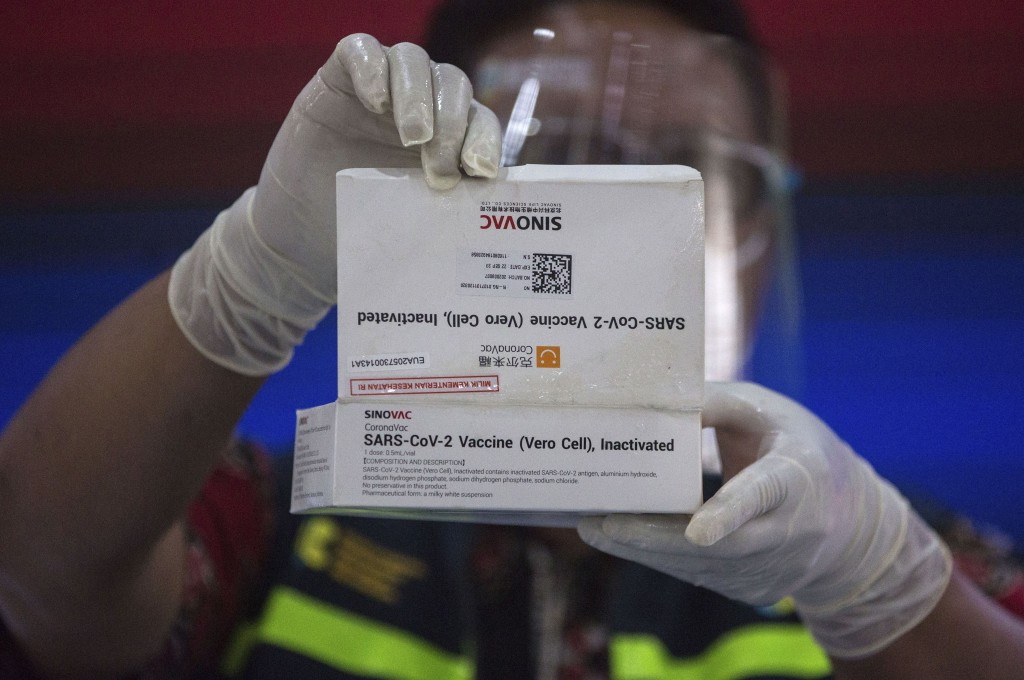 A health worker shows a box of COVID-19 vaccine before giving an inoculation to a government official in Medan, North Sumatra, Indonesia, Thursday, Ja...