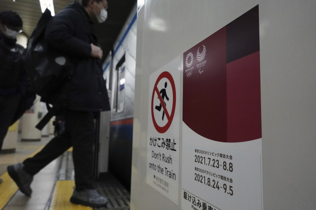 People wearing protective masks to help curb the spread of the coronavirus get on a subway with a banner of Tokyo 2020 Olympic and Paralympic games in...
