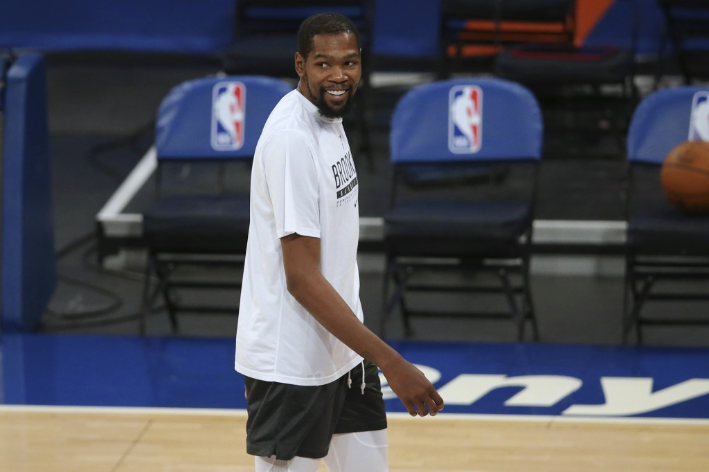 Brooklyn Nets forward Kevin Durant smiles as players warm up for the team's NBA basketball game against the New York Knicks on Wednesday, Jan. 13, 202...