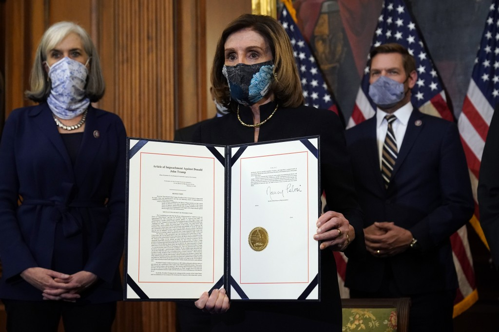 House Speaker Nancy Pelosi of Calif., displays the signed article of impeachment against President Donald Trump in an engrossment ceremony before tran...
