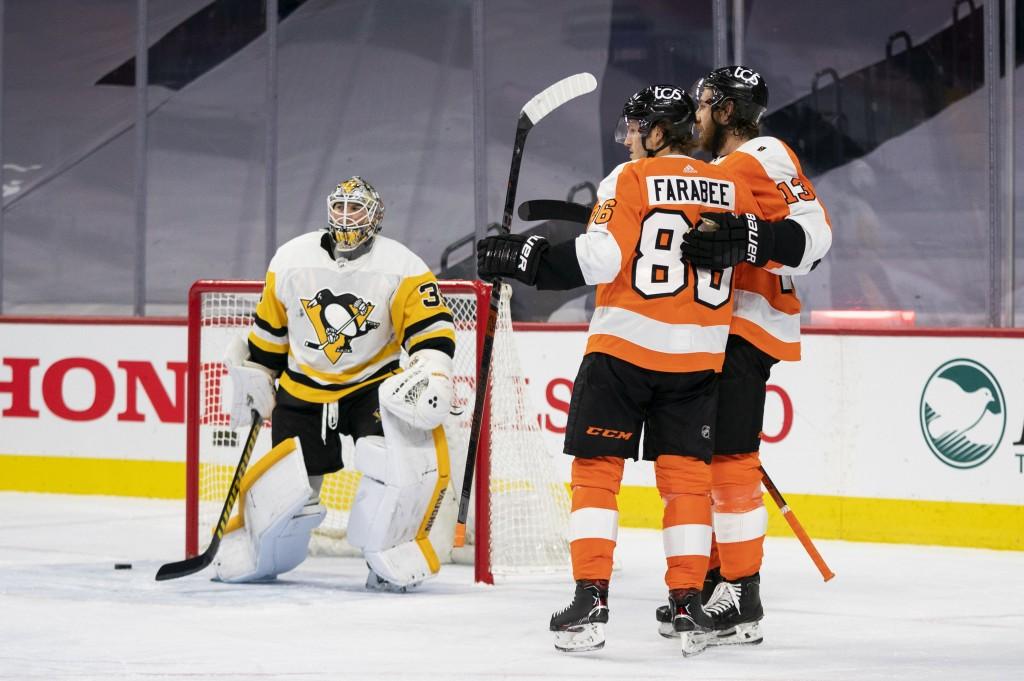 Philadelphia Flyers' Joel Farabee, center, celebrates his goal on Pittsburgh Penguins' goaltender Tristan Jarry, left, with Kevin Hayes, right, during...