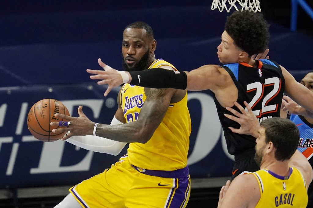 Los Angeles Lakers forward LeBron James, left, moves around Oklahoma City Thunder forward Isaiah Roby (22) during the first half of an NBA basketball ...