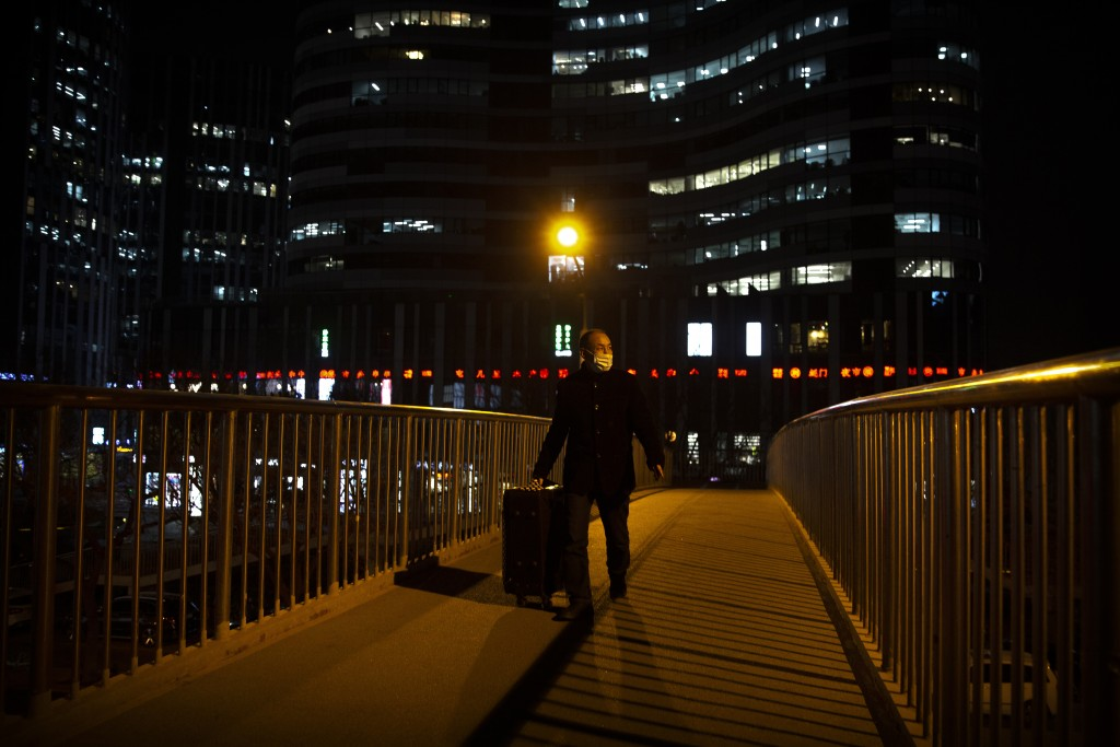 A man wearing a face mask to protect against the spread of the coronavirus wheels a suitcase across a pedestrian bridge in Beijing, Wednesday, Jan. 13...