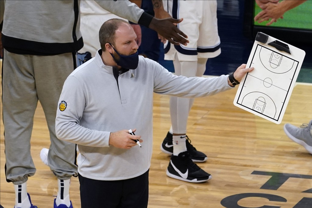 Memphis Grizzlies Taylor Jenkins holds the play board during a timeout in the first half of an NBA basketball game against the Minnesota Timberwolves,...