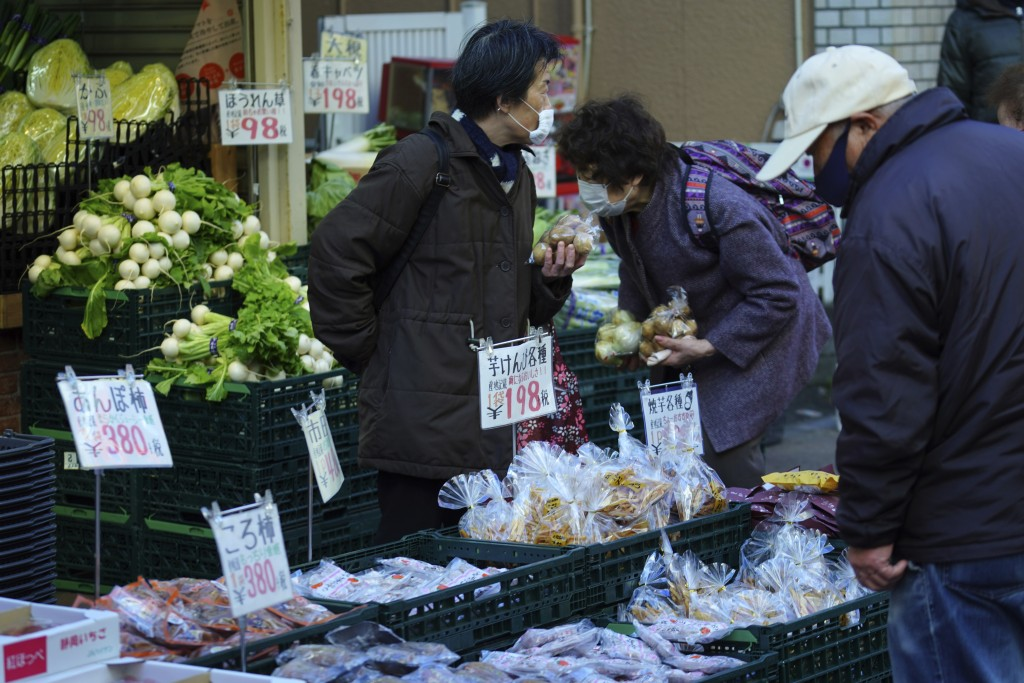 People wearing protective masks to help curb the spread of the coronavirus shop at a vegetable shop in Tokyo Thursday, Jan. 14, 2021. The Japanese cap...