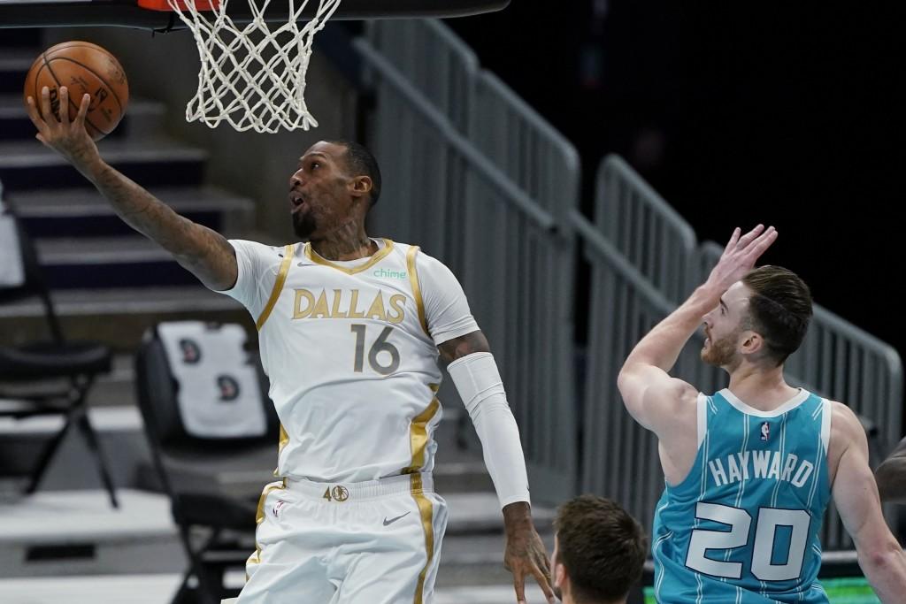 Dallas Mavericks forward James Johnson shoots past Charlotte Hornets forward Gordon Hayward during the first half of an NBA basketball game in Charlot...